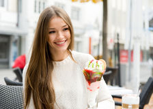 Taking the rest after shopping. Young woman happy sitting in street cafe with ice cream Stock Image