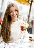 Taking the rest after shopping. Young woman happy sitting in street cafe with ice cream Royalty Free Stock Photography