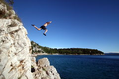 Taking A Risk. A young man jumps from a cliff into the sea Stock Images