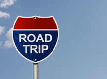 Taking a road trip. An interstate road sign that is red and blue with words Road Trip over a sky background, Taking a road trip royalty free stock photo