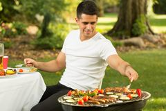 Taking a seconds. Hungry young man taking a seconds of barbecue food royalty free stock images