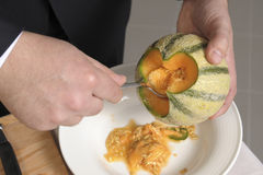 Taking the seeds out of the melon Stock Images