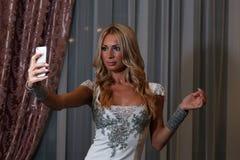 Taking selfi. Blonde taking selfie and posing in restaurant stock images