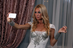Taking selfi. Blonde taking selfie and posing in restaurant Royalty Free Stock Photography