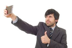 Taking a selfie. Businessman in suit and tie taking selfie photo with mobile phone camera posing happy and successful isolated on white background Stock Photos