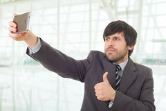 Taking a selfie. Businessman in suit and tie taking selfie photo with mobile phone camera posing happy and successful at the office Stock Photography