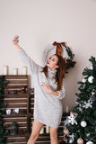 Taking selfie by Christmas tree. Royalty Free Stock Photography