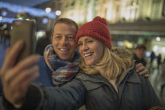 Taking a selfie in the City Centre at Christmas!. Taking a selfie together in the middle of the city centre, all wrapped up in their warm clothes because of the Royalty Free Stock Image