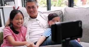 Taking a selfie with Dad. Father and his two children are taking a selfie at home with a smart phone on a selfie stick stock video footage