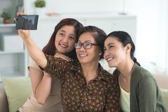 Taking selfie with daughters. Senior women taking selfie with her two daughters Stock Photos