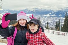 Taking selfie! Family.Happy mother and little boy making self portrait in the winter mountains. Woman holding smartphone camera. Panorama of Zakopane city in Stock Image