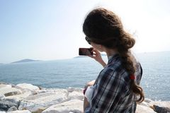 Taking Selfie. Girl takes selfie at the seaside in the face of princes islands istanbul, turkey Stock Images