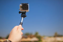 Taking selfie. Hand with photo camera on monopod royalty free stock photos