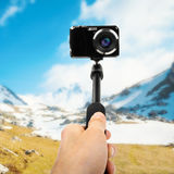 Taking selfie - hand with photo camera on monopod Royalty Free Stock Image