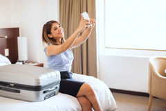 Taking selfie of her first business trip. Pretty young businesswoman taking a selfie after arriving at a hotel to remember her first business trip Stock Image