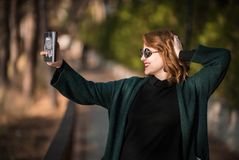 Taking Selfie Snapshot with Attitude. Woman with Smartphone at the Park Stock Photo