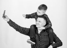 Taking selfie with son. Child riding on dads shoulders. Happiness being father of boy. Having fun. Fathers day. Father. Example of noble human. Father little stock images