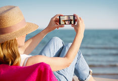 Taking a selfie on their phone at the beach Stock Photo