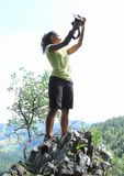 Taking selfie on top of rock in Slovak Paradise. Papuan young woman - tropical girl standing on top of viewpoint and taking selfie with hills with forest in stock photo