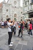 Taking selfies in front of Cathedral Florence. Young People taking photos in front of Cathedral Santa Maria del Fiori Florence, Italy stock photo