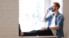 Taking Sip of Coffee, Sitting in Window, Red Hairs and Beard Royalty Free Stock Photography