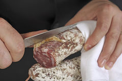 Taking the skin off a dried sausage Stock Photos