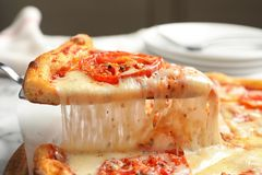 Taking slice of hot cheese pizza Margherita on table. Closeup stock photography