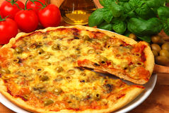 Taking a slice of pizza. Taking a slice of a pizza with olives and mozzarella cheese stock images