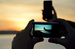 Taking smart phone photo with digital camera royalty free stock photography