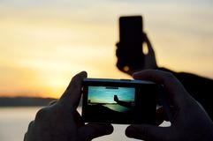 Taking smart phone photo with digital camera stock images