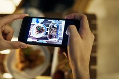 Taking smartphone photo of a dinner plate social media concept Stock Photos