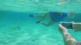 Taking smartphone underwater to get a nice shot. Slow motion of two people diving to get good underwater shot. Woman using smartphone in water-proof case to take stock footage