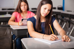 Taking some notes in class. Pretty high school student taking some notes during class stock photo