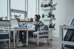 Taking some time to think. Thoughtful young man holding a cup and looking outside while sitting on the sofa Stock Image