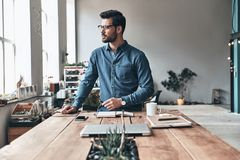 Taking some time to think. Thoughtful young man looking away while working in the creative working space Royalty Free Stock Photos