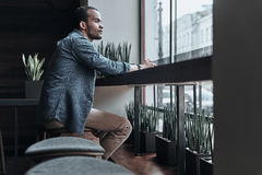Taking some time to think. Thoughtful young man looking outside while sitting in the cafeteria Royalty Free Stock Image