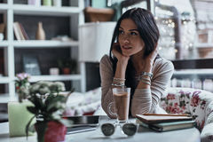 Taking some time to think. Thoughtful young woman looking away while sitting in restaurant Stock Photography