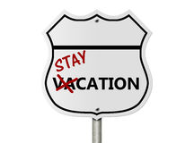 Taking a stay-cation. An American interstate road sign with words stay-cation isolated over white, Taking a stay-cation Royalty Free Stock Image