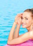 Taking sunbath in bikini. Cute young woman taking sunbath at the pool royalty free stock image