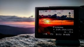 Taking sunset photo with a camera in the mountains. Taking sunset  photo with a camera in the mountains Royalty Free Stock Photography