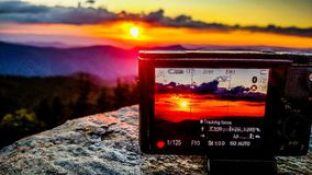 Taking sunset photo with a camera in the mountains Stock Photos