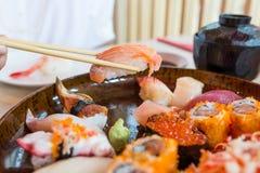 Taking sushi with chopsticks stock photography
