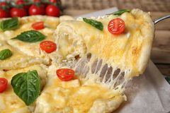 Taking tasty homemade pizza slice with melted cheese. Closeup stock photography