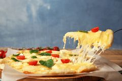 Taking tasty homemade pizza slice with melted cheese. On table royalty free stock photos