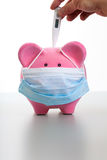Taking Temperature from a sick Piggy - Swine Flu Concept. Pink piggy bank wearing a protective face mask. Hand holding a thermometer to measure temperature or Royalty Free Stock Photo