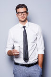 Taking time for coffee break. Confident young man in shirt and tie holding coffee cup and looking at camera while standing against grey background Royalty Free Stock Images