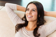 Taking time to have a break. Top view of attractive young woman looking at camera and smiling while relaxing on the couch at home Stock Photos