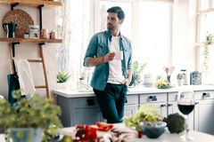 Taking time to think. Handsome young man in casual wear looking away and having a hot drink while standing in the kitchen at home royalty free stock photo