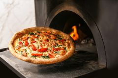 Taking traditional pizza out of oven. In restaurant kitchen stock images