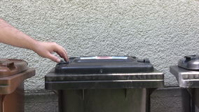 Taking the Trash Out. Person putting a full trash bag into a waste container. Canon HV30. HD 16:9 1920 x 1080 at 25.00 fps. Progressive scan. Photo JPG stock footage